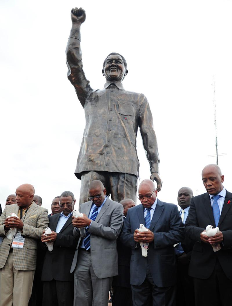 CORRECTS YEAR  A giant statue of former president Nelson Mandela after being unveiled on Naval Hill in Bloemfontein, South Africa, Thursday, Dec 13, 2012, by president Jacob Zuma, second from right, ahead of the ruling African National Congress's elective conference. Mandela, who has been hospitalized since the weekend, is recovering from a lung infection. (AP Photo)