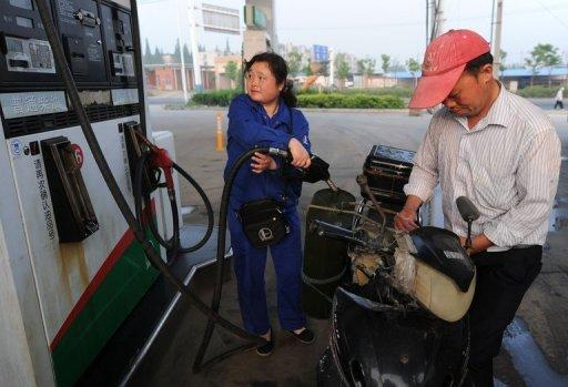A motorcyclist fills up at a petrol station in Hefei