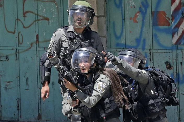 Three members of the Israeli security forces.  One fires tear gas.