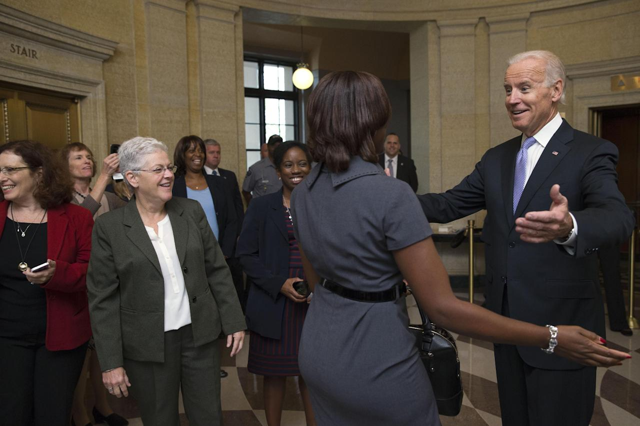 Vice President Joe Biden, right, greets Environmental Protection Agency workers as they return to work after 16 days of a government shutdown at the William Jefferson Clinton Federal Building in Washington on Thursday, Oct. 17, 2013. Thousands of furloughed federal workers returned to work across the country Thursday after 16 days off the job due to the partial government shutdown. (AP Photo/Jacquelyn Martin)