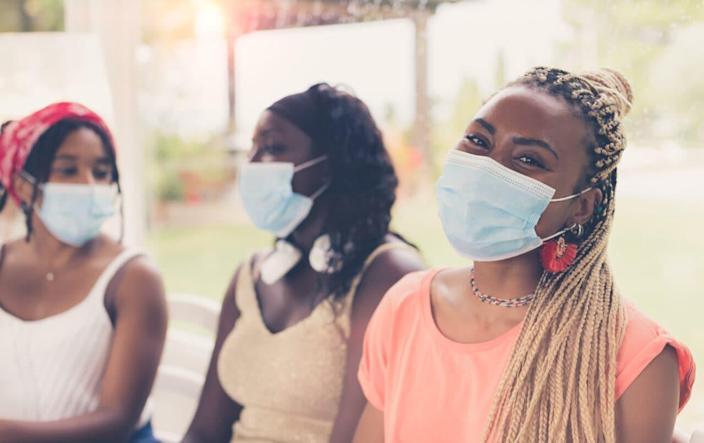 Close-up of three African American girls wearing surgical masks. 3 young women sitting together using coronavirus protection measures after or during quarantine. (Credit: Adobe Stock)