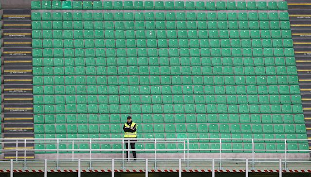 A steward looks on from an empty stand during the Serie A match between AC Milan and Genoa CFC which is being played in a closed stadium at Stadio Giuseppe Meazza on March 8, 2020 in Milan, Italy. (Photo by Marco Luzzani/Getty Images)