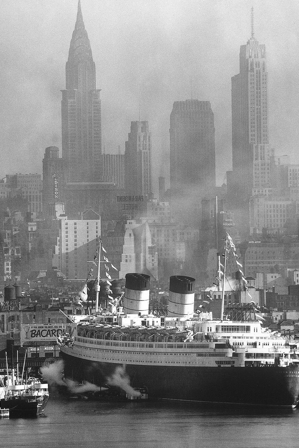 <p>View of the ocean liner, the Queen Elizabeth of the Cunard line, as it sails into port with the Chrysler Building, the Chanin Building, and 500 Fifth Avenue spotted in the background. </p>