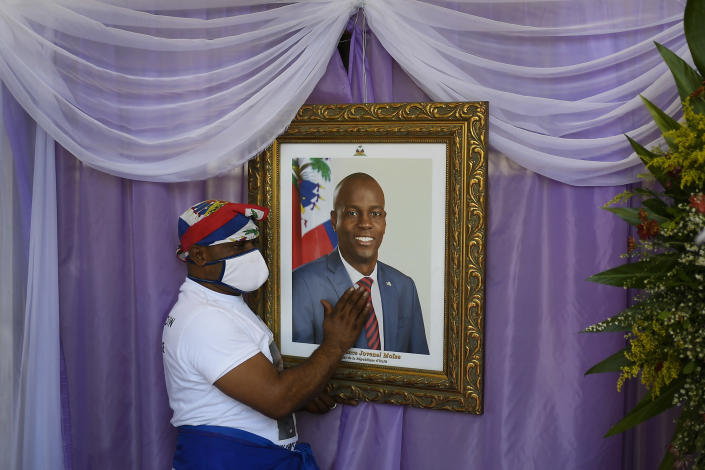 A man touches a portrait of the late Haitian President Jovenel Moïse outside the Cathedral where a memorial service for him takes place in Cap-Haitien, Haiti, Thursday, July 22, 2021. Moïse was killed in his home on July 7. (AP Photo/Matias Delacroix)
