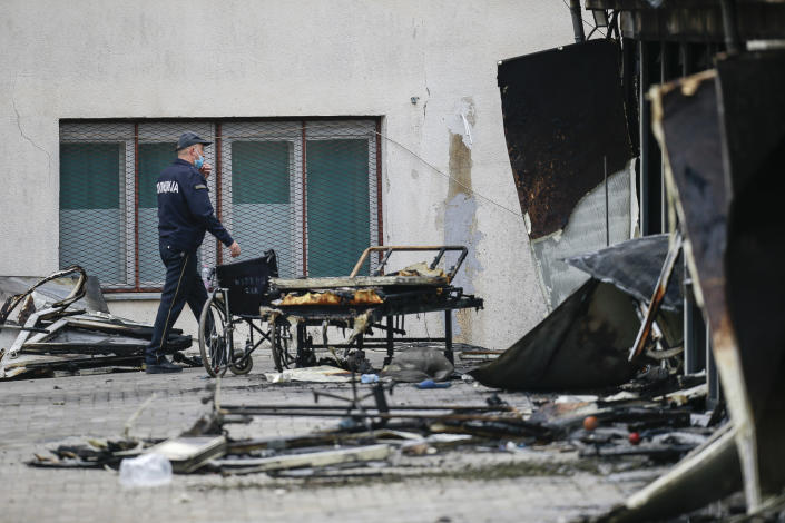 A police officer walks past burned hospital equipment on the site of a destroyed field hospital following a fire in North Macedonia's northwestern city of Tetovo, early Thursday, Sept. 9, 2021. The government of North Macedonia will hold an emergency meeting Thursday over a fire overnight that ripped through a field hospital set up to treat COVID-19 patients, leaving numerous people dead. (AP Photo/Visar Kryeziu)