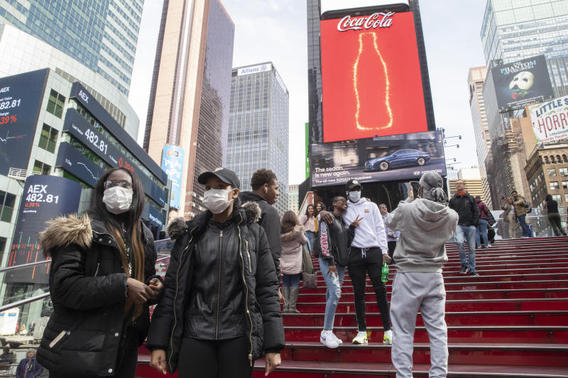 A group of visitors from Philadelphia wear masks as a precaution to the coronavirus, Wednesday, March 11, 2020, in New York's Times Square. New York Gov. Andrew Cuomo said Wednesday he will ask business owners to stagger their employees' work shifts or let them work from home to reduce potential coronavirus exposures.  (AP Photo/Mary Altaffer)