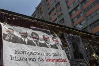 A banner showing images of several Mexican former presidents, obscuring their eyes with red bars, and calling for citizens to participate in a referendum on whether ex-presidents should be tried for their alleged crimes during their time in office, hangs from a wall in Mexico, City. Sunday, Aug. 1, 2021. (AP Photo/Christian Palma)