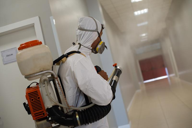 BRASILIA, BRAZIL - JULY 31: A sanitation worker wearing PPE disinfects common areas of a public school amidst the coronavirus (COVID-19) pandemic at the Candangolância on July 21, 2020 in Brasilia. The government of the capital of Brazil intends to return to face-to-face classes in August as the country reports over 2.610,000 confirmed positive cases of Coronavirus and reports over 91,263 deaths. (Photo by Andressa Anholete/Getty Images)
