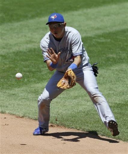 Toronto Blue Jays shortstop Munenori Kawasaki fields a ball hit by Cleveland Indians' Asdrubal Cabrera in the fifth inning of a baseball game, Thursday, July 11, 2013, in Cleveland. Cabrera was out on the play. (AP Photo/Tony Dejak)