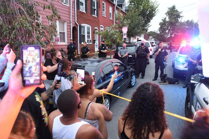People chant during a protest at the scene of a police shooting in Lancaster, Pennsylvania, on Sunday, Sept. 13, 2020. A man was shot by police earlier in the day after a reported domestic dispute, police said. A Lancaster city police officer fired at a 27-year-old man who was armed with a knife. The man, identified as Ricardo Munoz, was killed and pronounced dead at the scene.