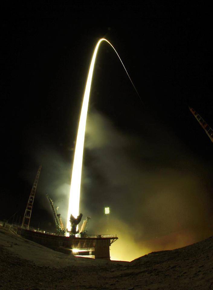 In this photo taken with a fisheye lens and with long time exposure the Soyuz-FG rocket booster with Soyuz TMA-08M space ship carrying a new crew to the International Space Station, ISS, blasts off at the Russian leased Baikonur cosmodrome, Kazakhstan, early Friday, March 29, 2013. The Russian rocket carries Russian Cosmonauts Alexander Misurkin and Pavel Vinogradov and U.S. astronaut Christopher Cassidy. (AP Photo/Dmitry Lovetsky)