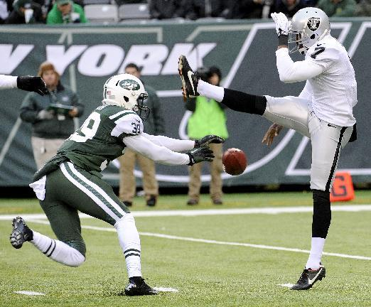 New York Jets free safety Antonio Allen, left, blocks a punt by Oakland Raiders punter Marquette King during the first half of an NFL football game on Sunday, Dec. 8, 2013, in East Rutherford, N.J. Allen recovered the ball in the end zone for a score during the play. (AP Photo/Bill Kostroun)