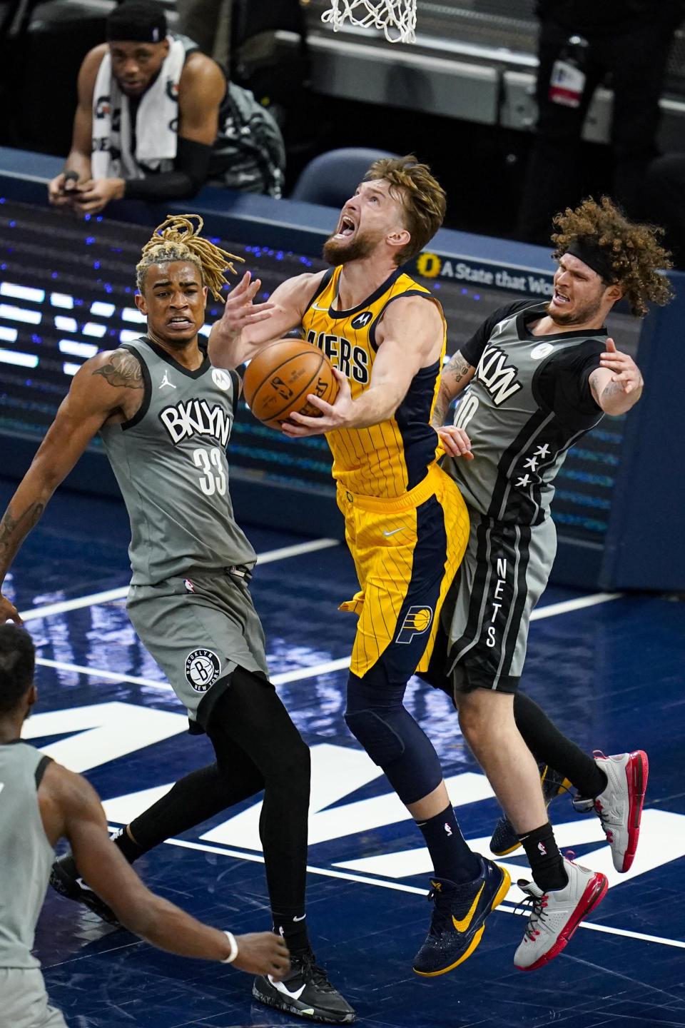 Indiana Pacers forward Domantas Sabonis (11) shoots between Brooklyn Nets forward Nicolas Claxton (33) and guard Tyler Johnson (10) during the second half of an NBA basketball game in Indianapolis, Wednesday, March 17, 2021. (AP Photo/Michael Conroy)