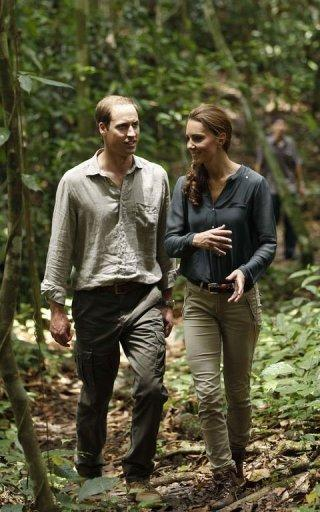 Prince William (L) and his wife Catherine, the Duchess of Cambridge, walk through the rainforest in Danum Valley Research Center on the island of Borneo on September 15