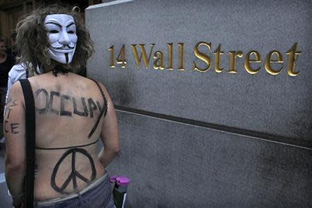 An Occupy Wall Street activist, wearing a Guy Fawkes mask, takes part in a march in downtown Manhattan in New York in this July 11, 2012 file photo.REUTERS/Eduardo Munoz/Files