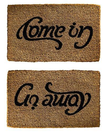 brown doormat that says come in and then go away depending on the angle