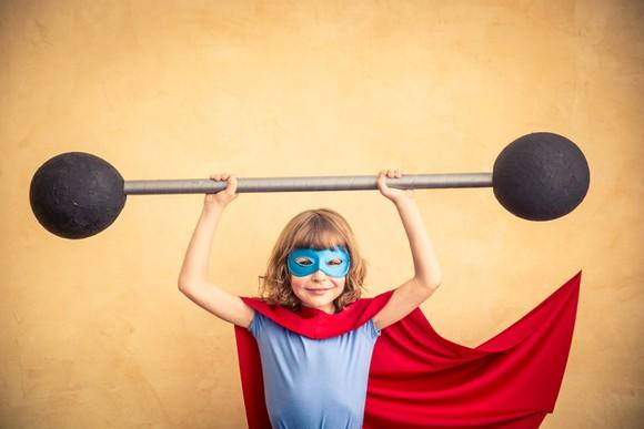 Child in super hero costume lifting foam barbell.