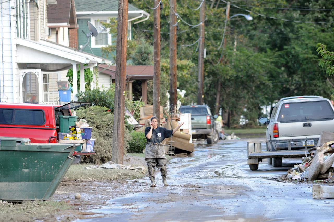 WEST PITTSTON, PA - SEPTEMBER 10: A woman talks on the phone near her flood damaged home September 10, 2011 in West Pittston, Pennsylvania. Major flooding along the Susquehanna River in the Wilkes-Barre area caused millions in damage.  (Photo by William Thomas Cain/Getty Images)