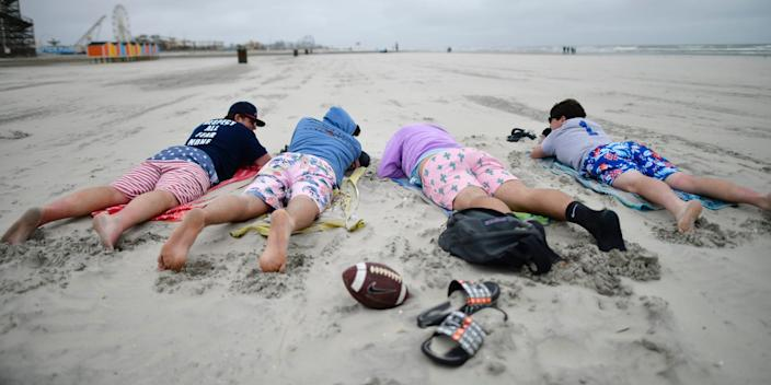 Friends gather on a cold and windy day at the beach May 24, 2020 in Wildwood, New Jersey. Governor Phil Murphy designated the state beaches open with restrictions during the Memorial Day weekend due to the coronavirus pandemic.