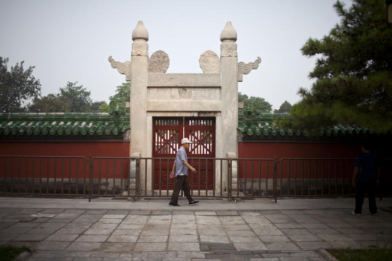 In this Tuesday, July 17, 2012 photo, a man walks past a gate to an ancient circular wall-enclosed altar, where emperors once made offerings to the sun, during his morning exercise at Ritan Park in Beijing, China. The park offers a window on daily Beijing life, starting at dawn with residents practicing tai chi and other exercises like walking backward or rubbing one's back against a tree. (AP Photo/Alexander F. Yuan)