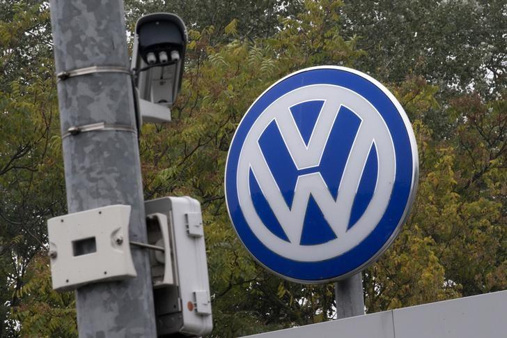 A Volkswagen logo stands next to a CCTV security camera in Wolfsburg