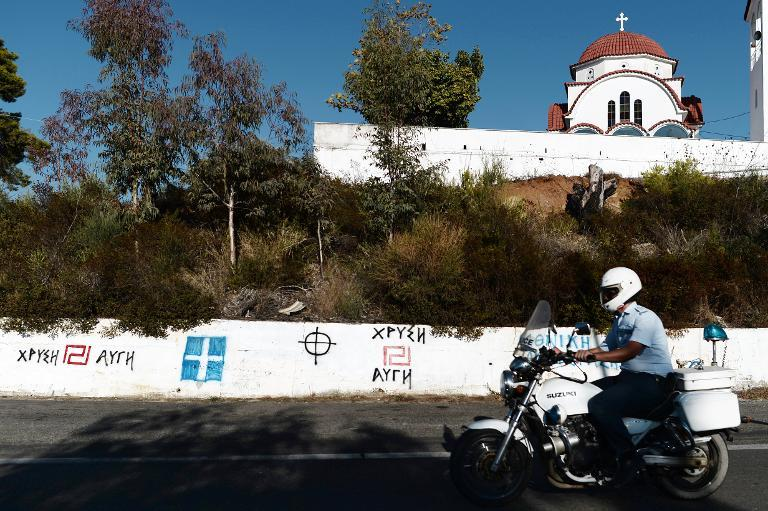 A policeman rides his motorcycle in front of Golden Dawn and nationalist graffiti in southern Greece, on September 29, 2013