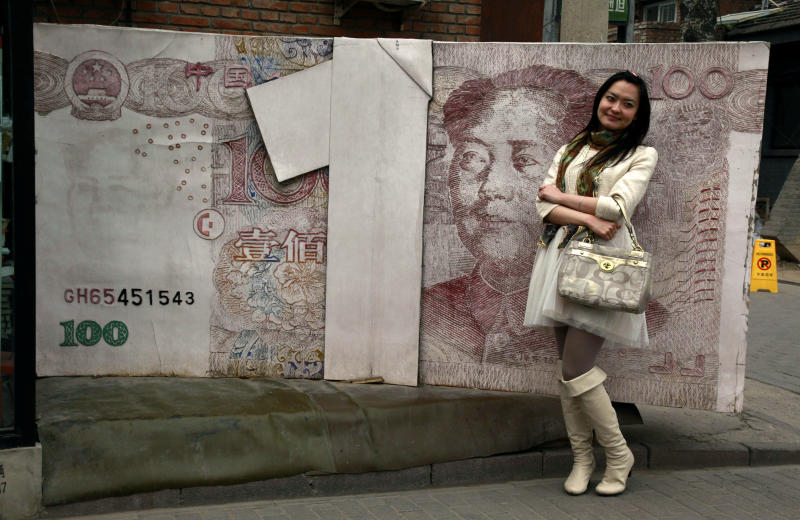 FILE - In this March 15, 2012 file photo, a Chinese woman poses for photos near a sculpture depicting a Chinese yuan note at an art district in Beijing, China. China's yuan has joined the ranks of the most traded currencies for the first time, underlining the growing might of the world's second-largest economy.(AP Photo/Ng Han Guan, File)