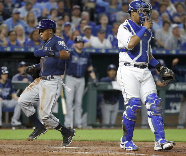 Tampa Bay Rays' Mallex Smith runs home past Kansas City Royals catcher Salvador Perez to score on a sacrifice bunt by Jesus Sucre during the sixth inning of a baseball game Tuesday, May 15, 2018, in Kansas City, Mo. (AP Photo/Charlie Riedel)