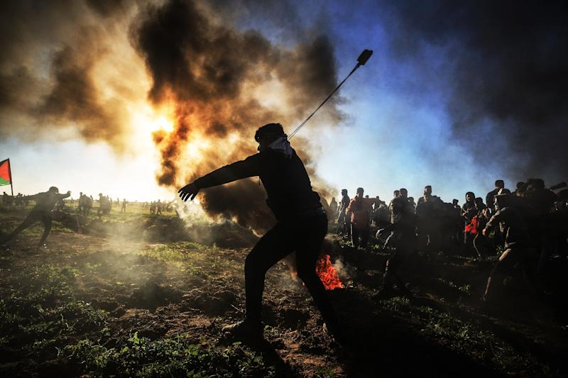 "A Palestinian throws a stone with a slingshot towards Israeli security forces during the ""Great March of Return"" demonstration near the Shuja'iyya neighborhood in Gaza City, Gaza on March 8, 2019. (Photo: Ali Jadallah/Anadolu Agency/Getty Images)"