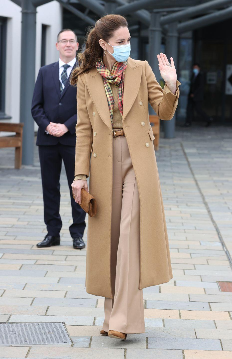 """<p>In her second monochromatic look of the week, Kate chose an all-camel outfit to continue <a href=""""https://www.townandcountrymag.com/society/tradition/g36519274/prince-william-kate-middleton-scotland-trip-2021-photos/"""" rel=""""nofollow noopener"""" target=""""_blank"""" data-ylk=""""slk:her tour of Scotland."""" class=""""link rapid-noclick-resp"""">her tour of Scotland.</a> The Duchess paired a double-breasted Massimo Dutti coat with khaki-colored wide-leg trousers, a scoop-neck sweater, and a matching brown belt, pumps, and clutch. She accessorized with a scarf in Strathearn tartan, symbolizing the couple's title in Scotland: the Earl and Countess of Strathearn.</p><p><a class=""""link rapid-noclick-resp"""" href=""""https://go.redirectingat.com?id=74968X1596630&url=https%3A%2F%2Fwww.tedbaker.com%2Fus%2FWomens%2FClothing%2FJackets-Coats%2FYECARA-Double-Breasted-Peaked-Lapel-Coat-Camel%2Fp%2F252384-CAMEL&sref=https%3A%2F%2Fwww.townandcountrymag.com%2Fstyle%2Ffashion-trends%2Fnews%2Fg1633%2Fkate-middleton-fashion%2F"""" rel=""""nofollow noopener"""" target=""""_blank"""" data-ylk=""""slk:Shop a Similar Coat"""">Shop a Similar Coat</a></p>"""