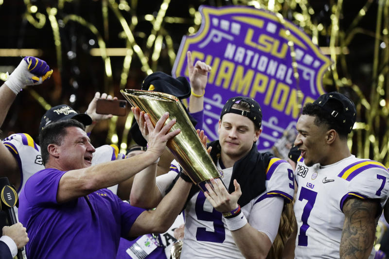 LSU head coach Ed Orgeron, left, and quarterback Joe Burrow, center, hold the trophy beside safety Grant Delpit after a NCAA College Football Playoff national championship game against Clemson, Monday, Jan. 13, 2020, in New Orleans. LSU won 42-25. (AP Photo/Sue Ogrocki)