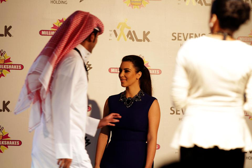 A Bahraini man walks off after having his picture taken with TV star Kim Kardashian, in Riffa, Bahrain, Dec. 1, 2012. Just hours after reality TV star Kim Kardashian gushed about her impressions of Bahrain, riot police fired tear gas to disperse more than 50 hardline Islamic protesters denouncing her presence in the Gulf kingdom .(AP Photo/Hasan Jamali)