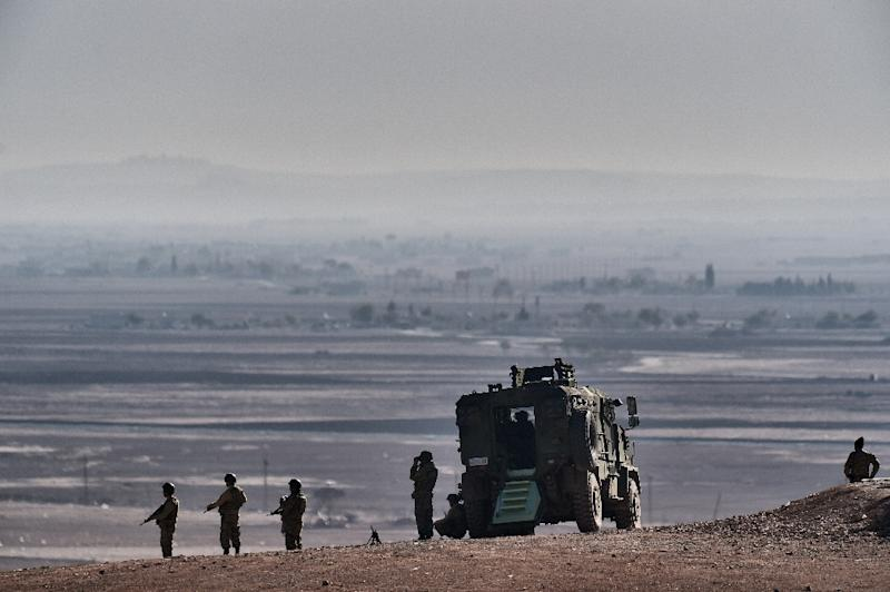 Turkish soldiers stand guard atop a hill opposite the city of Kobane, also known as Ain al-Arab, in the Turkish border village of Mursitpinar, Sanliurfa province, on November 10, 2014