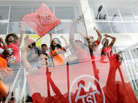 """Members of Homeless Workers Movement (MTST) shout slogans as they leave the beachside apartment """"Solaris"""" in Guaruja, Brazil April 16, 2018. REUTERS/Paulo Whitaker     TPX IMAGES OF THE DAY"""