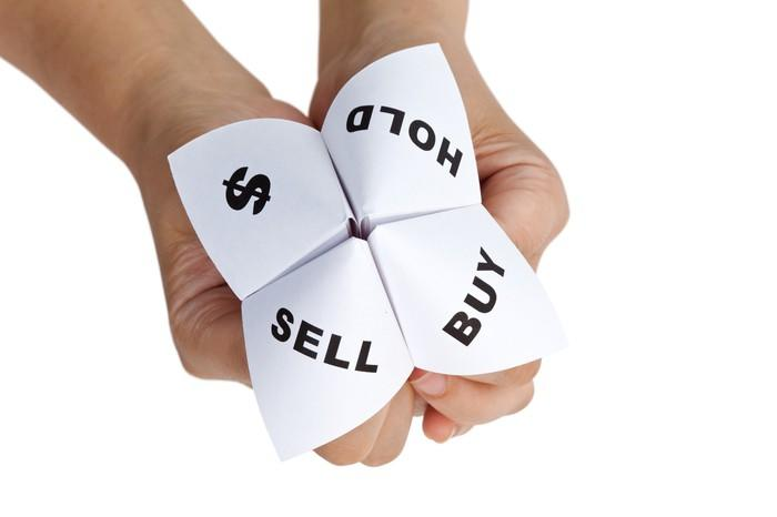 Hands holding fortune-telling folded paper with options of buy, sell, hold, and a dollar sign.