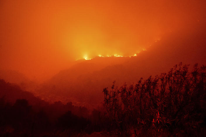 Flames from the KNP Complex Fire burn along a hillside above the Kaweah River in Sequoia National Park, Calif., on Tuesday, Sept. 14, 2021. The blaze is burning near the Giant Forest, home to more than 2,000 giant sequoias. (AP Photo/Noah Berger)