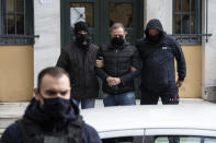 Plain clothed police officers escort handcuffed well-known actor and director Dimitris Lignadis, center, as they leave a magistrate's office in Athens, Sunday, Feb. 21, 2021. Lignadis, 56, the former artistic director of Greece's National Theatre, has been arrested on rape charges, police say. (AP Photo/Yorgos Karahalis)