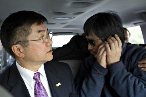 In handout photograph from the US Embassy Beijing Press office, Chinese dissident Chen Guangcheng speaks on a phone as US Ambassador to China Gary Locke (L) looks on, in Beijing. Chen appealed to US President Barack Obama to help get him and his family out of China, saying he fears for his life just hours after leaving the US embassy in Beijing