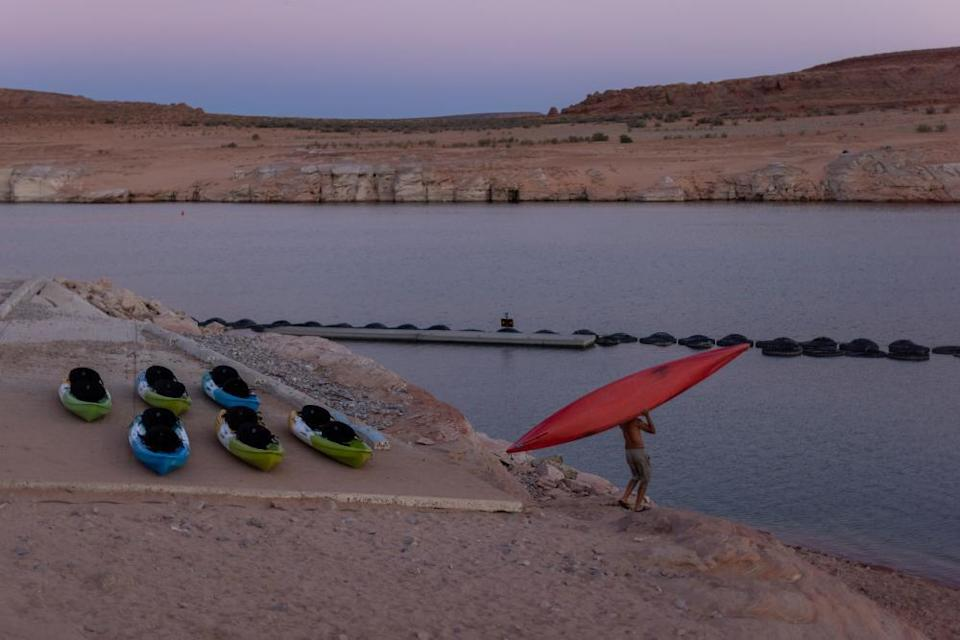 A kayaker climbs down the drop-off below the Antelope Point boat launch ramp which was made unusable by record low water levels.