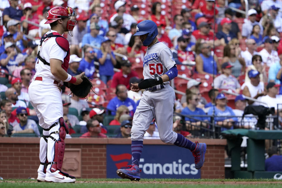 Los Angeles Dodgers' Mookie Betts (50) scores past St. Louis Cardinals catcher Andrew Knizner during the third inning of a baseball game Thursday, Sept. 9, 2021, in St. Louis. (AP Photo/Jeff Roberson)