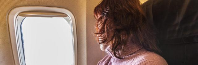 A woman is looking out the window of a plane.