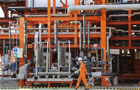 A worker walks past infrastructure on D Island, the main processing hub, at the Kashagan offshore oil field in the Caspian sea in western Kazakhstan