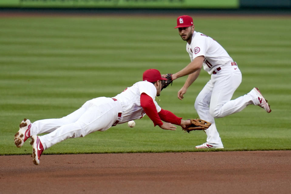 St. Louis Cardinals third baseman Nolan Arenado, left, dives but is unable to reach a single by Colorado Rockies' Garrett Hampson as Cardinals shortstop Paul DeJong, right, backs up the play during the first inning of a baseball game Friday, May 7, 2021, in St. Louis. (AP Photo/Jeff Roberson)
