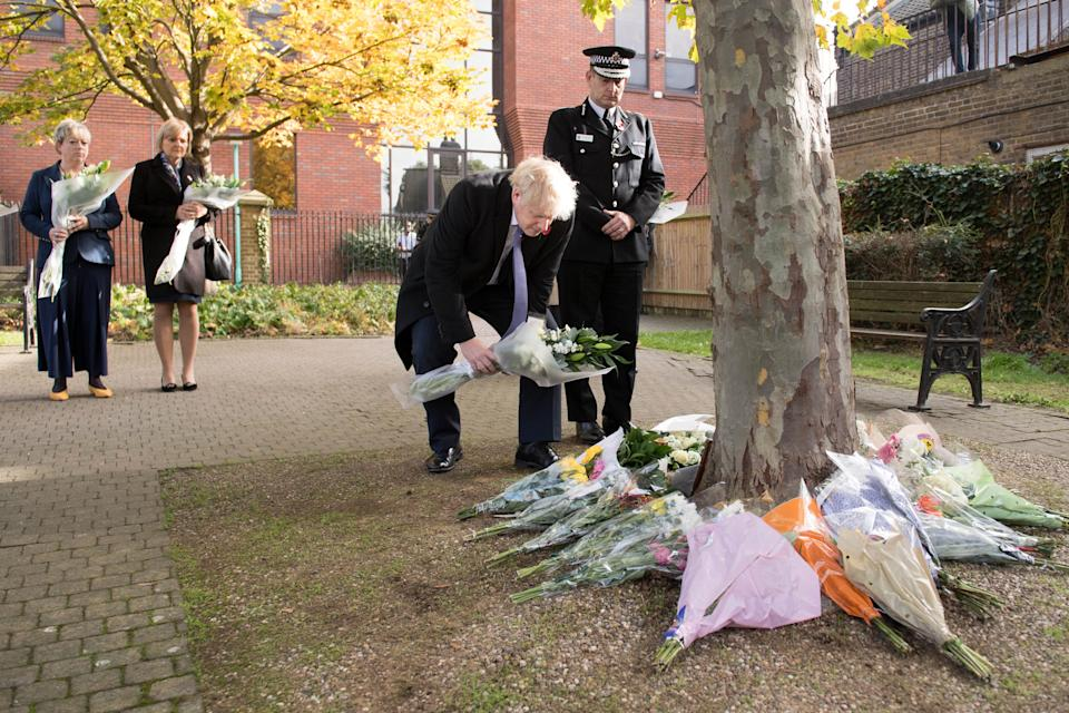 Britain's Prime Minister Boris Johnson stands with Chief Constable of Essex Police, Ben-Julian Harrington (R), as he lays flowers, during a visit to Thurrock Council Offices in Thurrock, east of London on October 28, 2019, following the October 23, 2019, discovery of 39 bodies concealed in a lorry. - British police investigating the deaths of 39 people in a refrigerated truck charged the driver on Saturday with manslaughter and people trafficking, as families in Vietnam expressed fear their loved ones were among the dead. (Photo by Stefan Rousseau / POOL / AFP) (Photo by STEFAN ROUSSEAU/POOL/AFP via Getty Images)