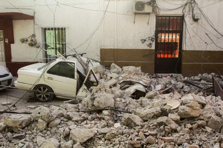 A car is crushed by debris from damaged houses in Jojutla de Juarez