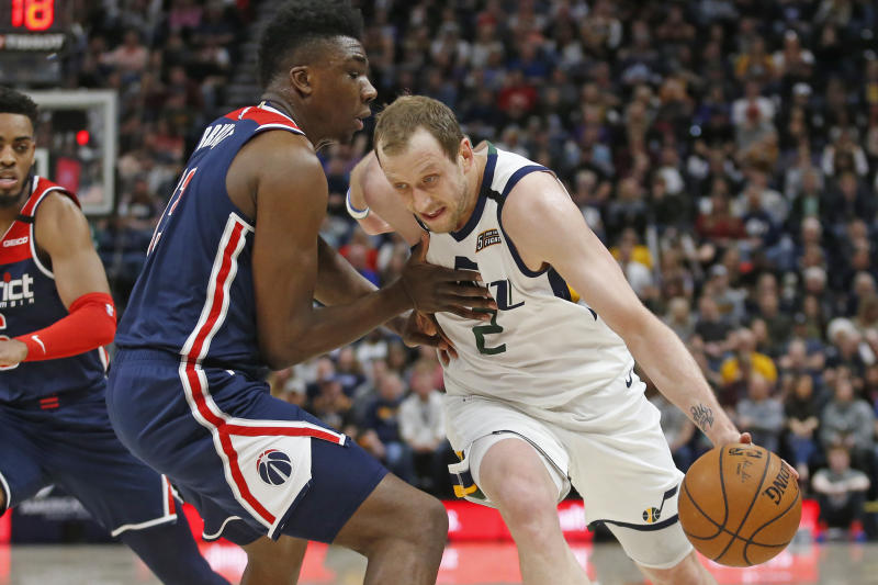 Utah Jazz guard Joe Ingles (2) drives around Washington Wizards center Thomas Bryant, left, in the first half during an NBA basketball game Friday, Feb. 28, 2020, in Salt Lake City. (AP Photo/Rick Bowmer)
