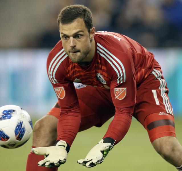 Vancouver Whitecaps goalkeeper Stefan Marinovic makes a save during the first half of an MLS soccer match against Sporting Kansas City in Kansas City, Kan., Friday, April 20, 2018. (AP Photo/Orlin Wagner)