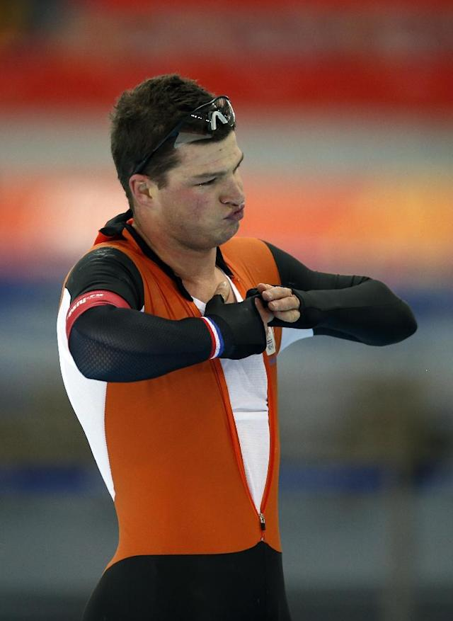 Sven Kramer of the Netherlands tugs on his suit after competing in the men's 10,000-meter speedskating race at the Adler Arena Skating Center during the 2014 Winter Olympics in Sochi, Russia, Tuesday, Feb. 18, 2014. (AP Photo/Pavel Golovkin)
