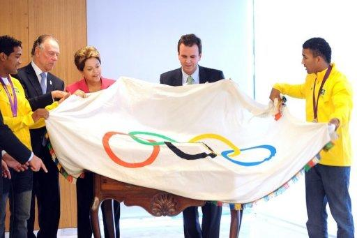 Brazilian President Dilma Rousseff (C) and others pose with the Olympic flag