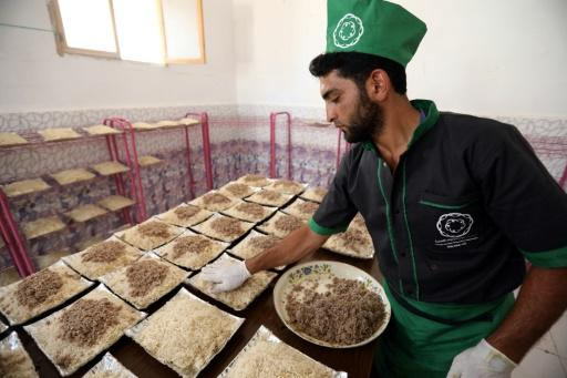 A worker plates food at a charity kitchen in Idlib on May 19, 2018, as they prepare iftar meals for Muslim devotees breaking their fast which are to be distributed to impoverished families, displaced from Ghouta